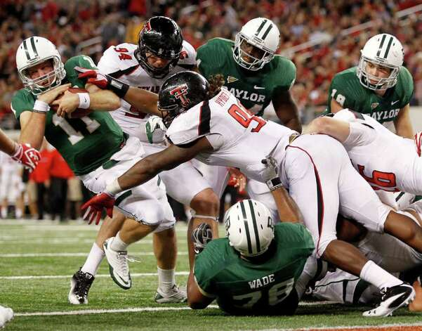 Baylor quarterback Nick Florence (11) scores a touchdown as Texas Tech's Scott Smith (94) and Kerry Hyder (91) defend in the fourth quarter of an NCAA college football game Saturday, Nov. 26, 2011, in Arlington, Texas. Baylor won 66-42. Photo: AP