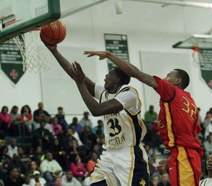 Westbury Christian's Brandon Jones (33) is fouled by Yate's Clyde Santee (32) as he drives to the ba