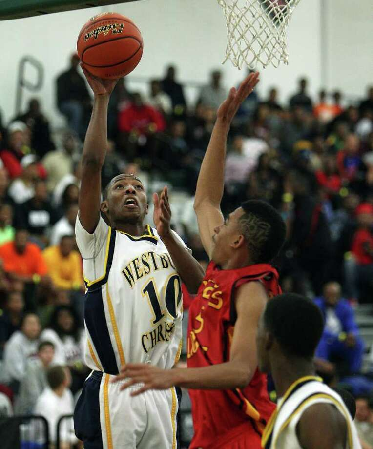 Westbury Christian's Darin Minniefield drives to the basket over Yate;s J.C. Washington during a high school basketball game between Yates and Westbury Christian at Strake Jesuit High as part of the Texas High School Jamboree November 26, 2011. Westbury Christian won 97-80. Photo: Bob Levey, Houston Chronicle / ©2011 Bob Levey
