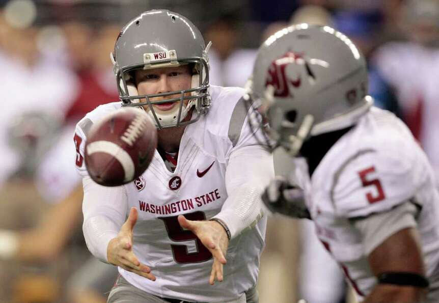 Washington State quarterback Marshall Lobbestael, left, flips the ball to running back Rickey Galvin