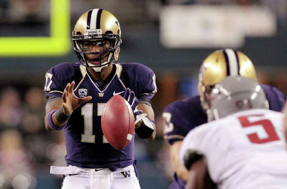Washington quarterback Keith Price, left, takes the hike against Washington State in the first half of an NCAA college football game on Saturday, Nov. 26, 2011, in Seattle. Photo: AP