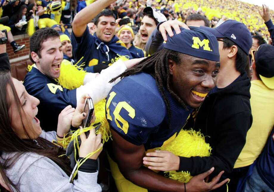 GREGORY SHAMUS : GETTY IMAGES HERE'S TO YOU, MR. ROBINSON: Michigan fans usually don't storm the field after beating a 6-6 team, but when that team is Ohio State and the Wolverines haven't won in the series since 2003, it's time to pour from the stands and mob quarterback Denard Robinson. Photo: Gregory Shamus / 2011 Getty Images