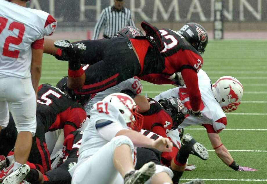 Memorial's defense takes down a Houston Memorial runner Saturday at Turner Stadium in Humble. Photo: Guiseppe Barranco, Guiseppe Barranco/The Enterprise / The Beaumont Enterprise