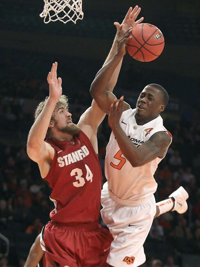 Stanford forward Andrew Zimmerman, left, blocks a shot by Oklahoma State guard Reger Dowell in the second half of an NIT Season Tip-Off college basketball tournament game at New York's Madison Square Garden, Wednesday, Nov. 23, 2011. Stanford won 82-67. (AP Photo/Richard Drew)  Ran on: 11-24-2011 Stanford forward Andrew Zimmerman gets in the way of Oklahoma State guard Reger Dowell. Ran on: 11-24-2011 Stanford forward Andrew Zimmerman gets in the way of Oklahoma State guard Reger Dowell. Photo: Richard Drew, AP