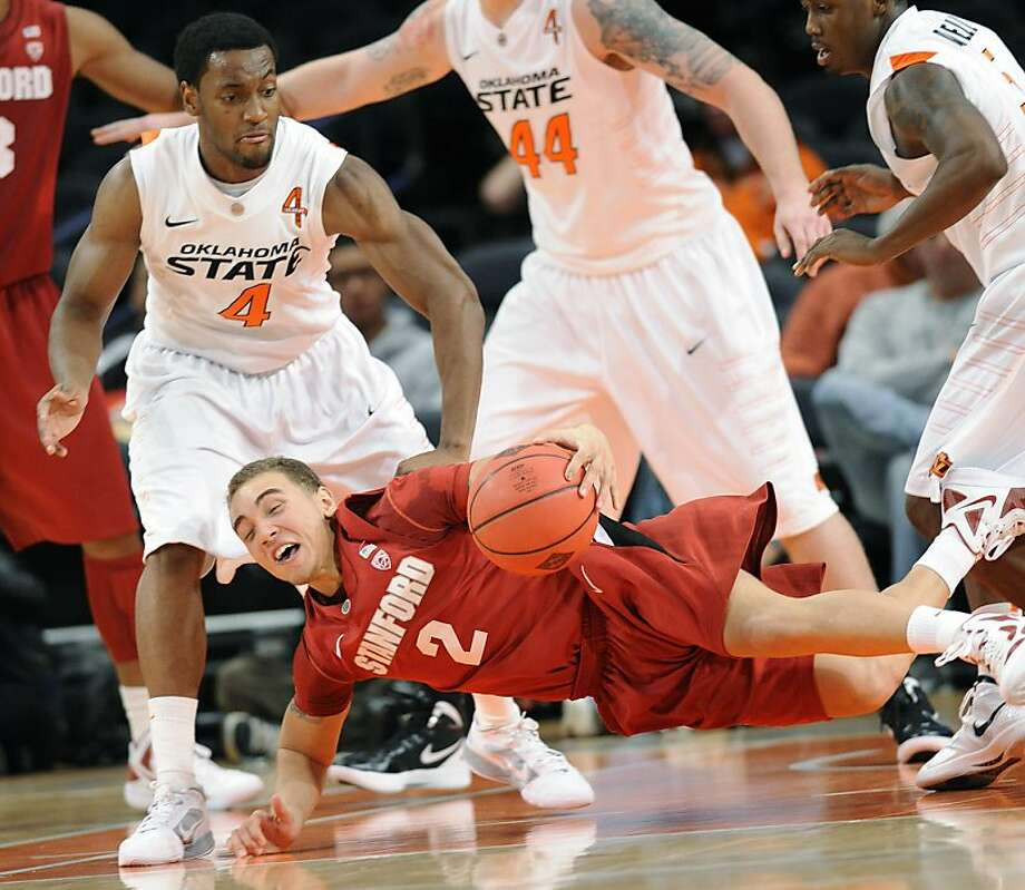 Stanford guard Aaron Bright (2) hits the floor as Oklahoma State guard Brian Williams (4) looks on during the first half of an NIT Season Tip-Off college basketball tournament game Wednesday, Nov. 23, 2011, at New York's Madison Square Garden. (AP Photo/Bill Kostroun) Photo: Bill Kostroun, AP