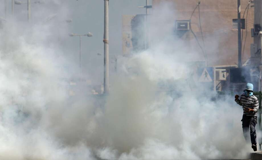 Anti-government protester runs from tear gas fired by riot police Wednesday, Nov. 23, 2011, in A'ali, Bahrain. (AP Photo/Hasan Jamali) Photo: Hasan Jamali, AP