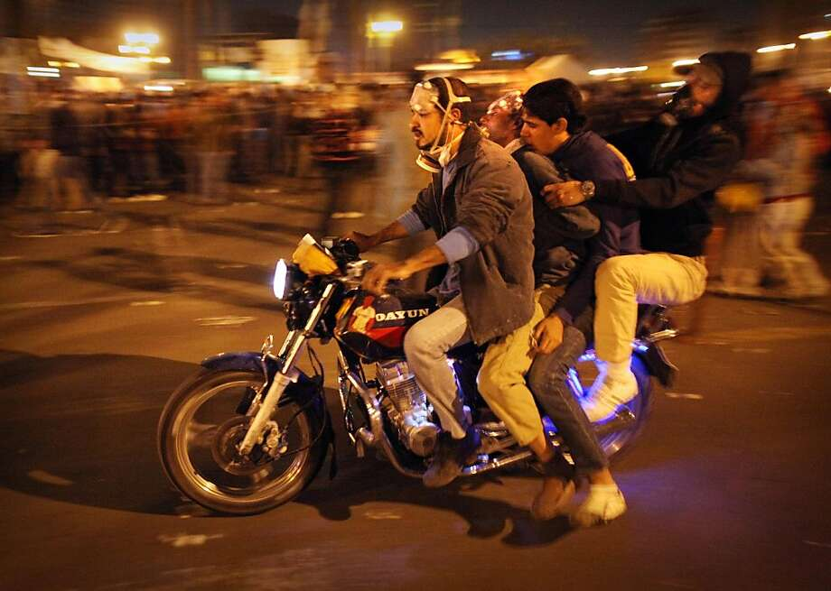 CAIRO, EGYPT - NOVEMBER 23:  A motorbike carries two injured protestors to a makeshift medical centre in Tahrir Square during clashes with police on November 23, 2011 in Cairo, Egypt. Thousands of Egyptians are continuing to occupy Tahrir Square after four days of clashes with security forces despite a promise from military leaders to bring forward Presidential elections.  (Photo by Peter Macdiarmid/Getty Images) Photo: Peter Macdiarmid, Getty Images