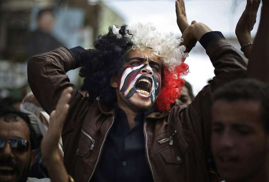 A protestor with Yemeni, Egyptian, Libyan, and Syrian flags painted on his face chants slogans during a demonstration against proposed immunity for Yemeni President Ali Abdullah Saleh under a deal for his resignation in Sanaa, Yemen, Wednesday, Nov. 23, 2011. Saleh plans to sign a deal Wednesday in the Saudi capital that could mean the end of his 33-year rule, the U.N. envoy to Yemen said. (AP Photo/Hani Mohammed) Photo: Hani Mohammed, AP
