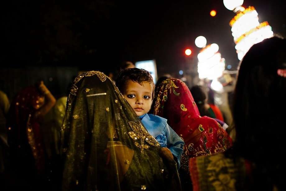 NEW DELHI, INDIA - NOVEMBER 23: A boy is carried through a wedding procession on November 23, 2011 in New Delhi, India. India's wedding season peaks from late October to early December each year as couples choose to wed in these auspicious months. The Indian wedding traditionally starts with a procession which sees the groom riding or drawn by a carriage with a white horse, escorted by close family and friends, a brass band and a mobile lighting crew powered by a diesel generator. Guests in attendance dance and celebrate through the streets, showering the groom with rupee notes, until they arrive to the final destination of the wedding. (Photo by Daniel Berehulak/Getty Images) Photo: Daniel Berehulak, Getty Images