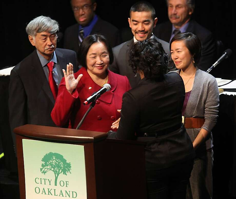 Oakland's new mayor Jean Quan (in red) is inaugurated by city clerk LaTonda Simmons (facing back) at Fox Theater in Oakland, Calif., on Monday, January 3, 2011.  Her family joined her with husband Floyd Huen (left) and her children William Huen and Lailan Huen at right. Photo: Liz Hafalia, The Chronicle