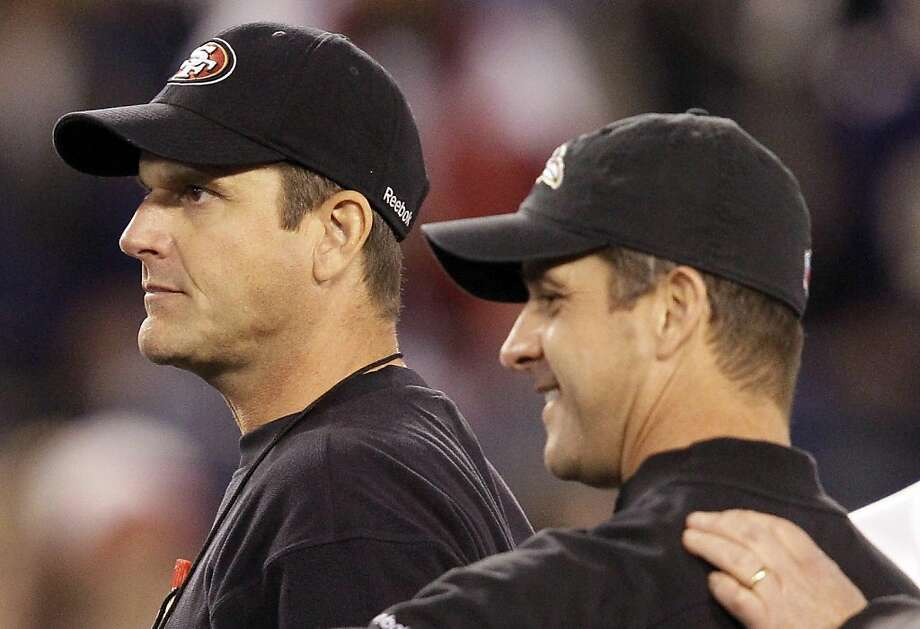 San Francisco 49ers head coach Jim Harbaugh, left, walks with his brother, Baltimore Ravens head coach John Harbaugh before an NFL football game in Baltimore, Thursday, Nov. 24, 2011. (AP Photo/Patrick Semansky) Photo: Patrick Semansky, AP