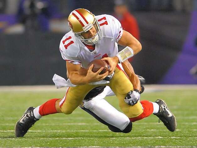 San Francisco 49ers quarterback Alex Smith is dragged down from behind by Baltimore Ravens linebacker Brendon Ayanbadejo in the second half of their game on Thursday, November 24, 2011, in Baltimore, Maryland. The Ravens come away with a 16-6 win over the 49ers.  (Doug Kapustin/MCT) Photo: Doug Kapustin, MCT