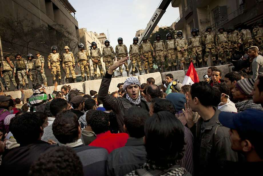 Egyptian Army soldiers stand guard atop a concrete block barricade while protesters chant slogans, near Tahrir Square, in Cairo, Egypt, Thursday, Nov. 24, 2011. Police and protesters demanding that Egypt's ruling military council step down are observing a truce after five days of deadly street battles in which dozens have died.  (AP Photo/Bernat Armangue) Photo: Bernat Armangue, AP