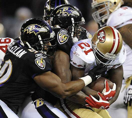 San Francisco 49ers running back Frank Gore (21) is tackled by Baltimore Ravens defenders in the first half of an NFL football game in Baltimore on Thursday, Nov. 24, 2011. (AP Photo/Nick Wass)  Ran on: 11-25-2011 Frank Gore is tackled by a flock of Ravens in the first half and finished the game with 39 yards on 14 carries. Photo: Nick Wass, AP