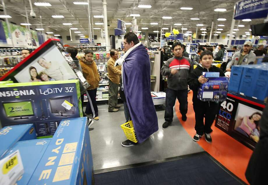 A shopper makes his way through the Best Buy store still wearing his blanket he wore while waiting out in the cold. Hundreds of shoppers at Best Buy in Pinole, Calif., waited in line (some for days) for the beginning of the holiday shopping season at midnight following Thanksgiving on Thursday, November 24, 2011. Photo: Carlos Avila Gonzalez, The Chronicle