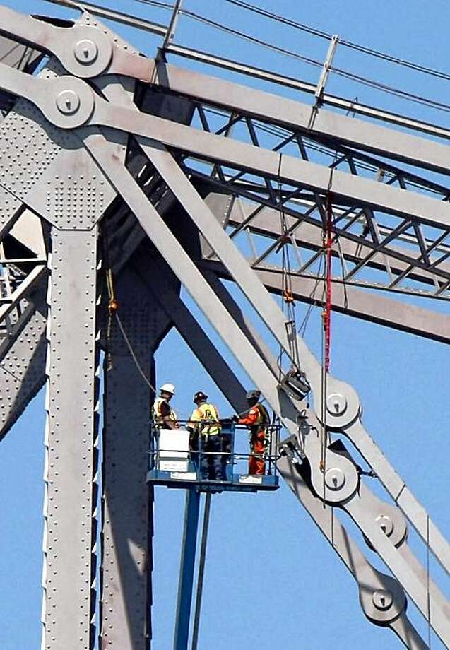 California Transportation Department workers survey a cracked steel link, called an eyebar, that helps hold up the Bay Bridge's east span. Sept 7, 2009. Photo: Lance Iversen, The Chronicle