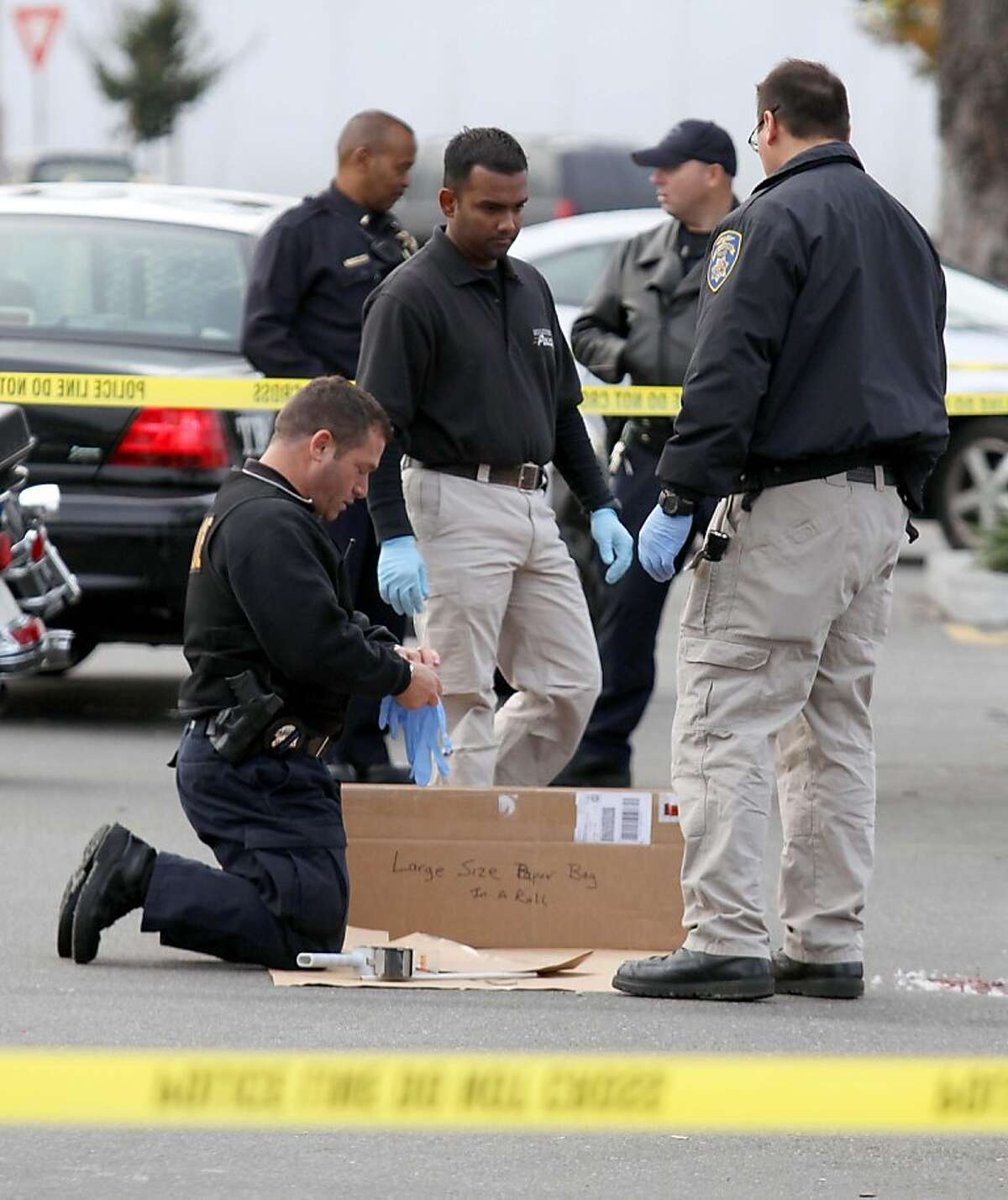 San Leandro police officers gather evidence at the scene of a shooting at Wal-Mart on Hesperian Boulevard, Friday, Nov. 25, 2011, in San Leandro, Calif. Gunfire rang out about 1:50 a.m. and a man was shot in a robbery attempt. Despite major injuries, police said he was in stable condition. (AP Photo/Bay Area News Group, Jane Tyska) MANDATORY CREDIT; MAGS OUT