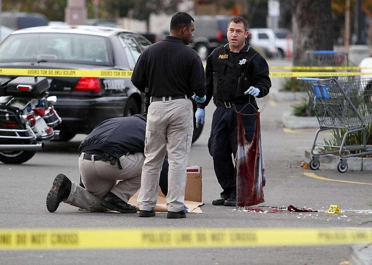 A San Leandro police officer, right, holds a bloody shirt as evidence is gathered at the scene of a shooting at Wal-Mart on Hesperian Boulevard, Friday, Nov. 25, 2011, in San Leandro, Calif. Gunfire rang out about 1:50 a.m. and a man was shot in a robbery attempt. Despite major injuries, police said he was in stable condition. (AP Photo/Bay Area News Group, Jane Tyska) MANDATORY CREDIT; MAGS OUT