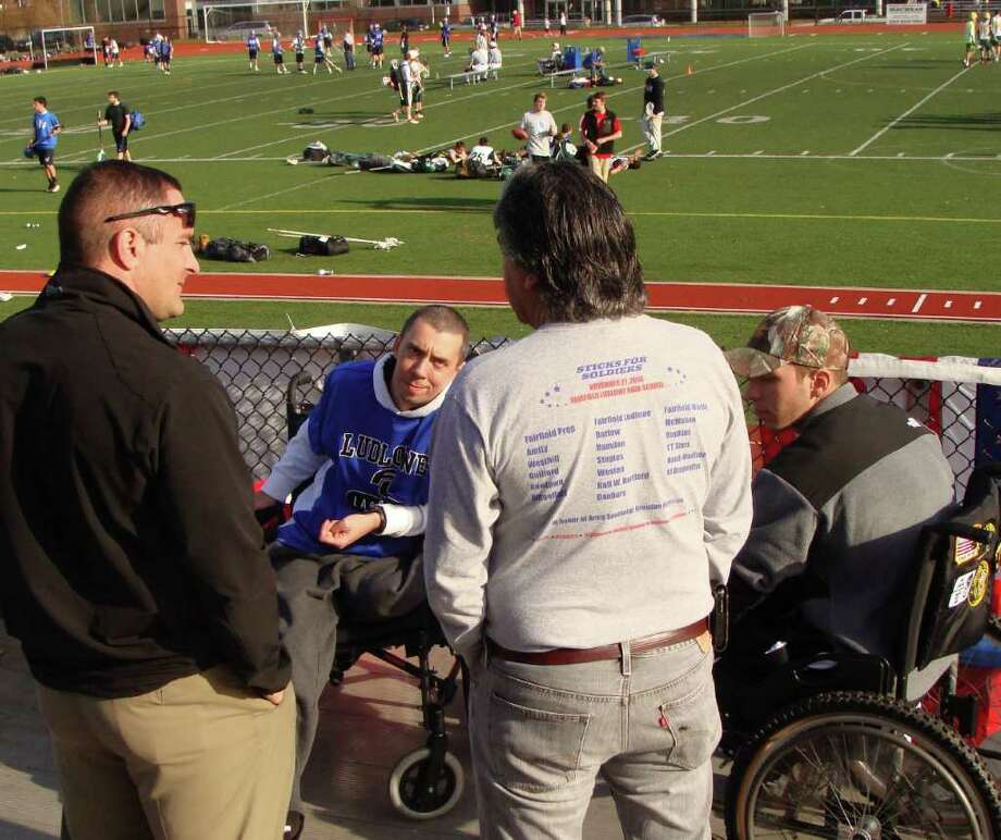 U.S. Marine Lt. Col. Thomas Armas, left with back to camera, of Fairfield, and Alex Marrocco, the father of last year's Sticks for Soldiers honoree Brendan Marrocco, talk Saturday with the three honorees of the 6th annual event, all three of whom use wheelchairs because of either injuries incurred or illness contracted during active duty in Iraq or Afghanistan. Two of the men are, Liam Dwye, center, a 30-year-old Southbury resident, and Joshua Budd, 19, of Cheshire, at far right. Lacrosse teams from around the region play on Fairfield Ludlowe High School's field, in background, to raise money for the cause. Photo: Meg Barone / Fairfield Citizen freelance