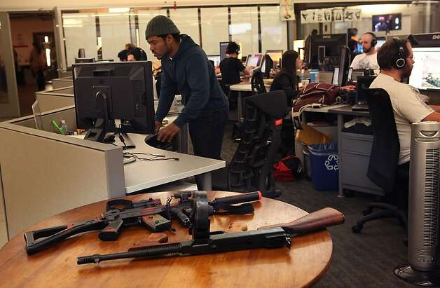 2-D artist Dennis Brown (left) working at the Mafia Wars office of Zynga in San Francisco, California, where a pair of toy guns are on a nearby table on Monday, October 3, 2011.  Ran on: 10-10-2011 Artist Dennis Brown (left) works on &quo;Mafia Wars 2,&quo; Zynga's first sequel, with a pair of toy guns on a table nearby. Photo: Liz Hafalia, The Chronicle