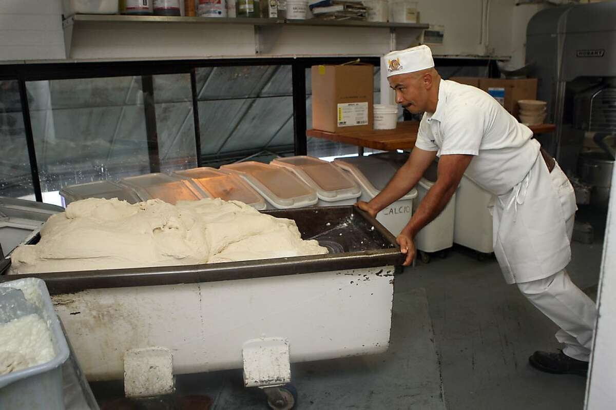 Alberto Garcia pushes a cart of dough to a shoot which will bring it to the divider in the downstairs kitchen at Boudin Bakery on 10th Ave. in San Francisco, California, on Wednesday, September 14, 2011.