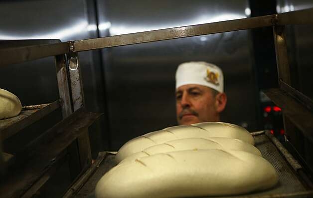Tony Gomez checking the loaves before placing them in the oven at Boudin Bakery on 10th Ave. in San Francisco, California, on Wednesday, September 14, 2011.  Tony has been working at Boudin for 18 years and helps bake 12,000 or more pieces daily. Photo: Liz Hafalia, The Chronicle