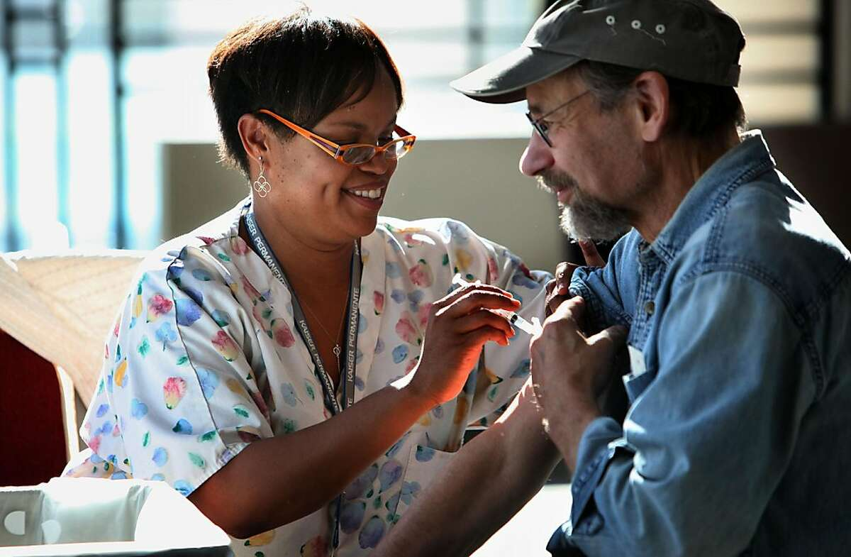 RN Christiane Tracy (left), giving a flu shot to Alan Kaplan (right), 62 years old from Oakland, at Kaiser in Oakland, Calif., on Friday, November 4, 2011.