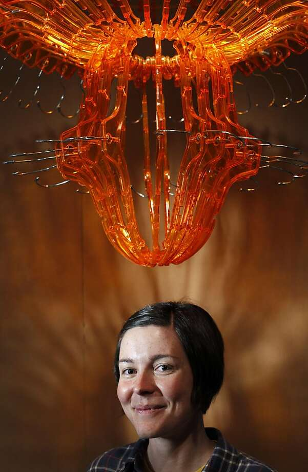 Nicole Catrett, exhibit developer, is part of the team that designs and builds the hands-on exhibits at the Tinkering Studio at the Palace of Fine Arts in San Francisco, Calif., Thursday, November 10, 2011.  She created the chandelier above her from plastic coat hangers. Photo: Sarah Rice, Special To The Chronicle