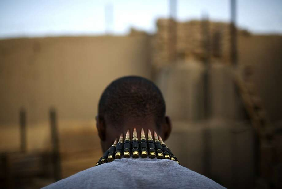 A string of bullets hangs on the neck of US Army soldier PFC Jean-Paul Desculline , of Miami, Florida, from 1-320th Alpha Battery, 2nd Brigade of the 101st Airborne Division, at COP Nolen, in the volatile Arghandab Valley, Kandahar, Afghanistan, Sunday, July 25, 2010. (AP Photo/Rodrigo Abd)  Ran on: 07-26-2010 Bullets hang from the neck of U.S. Army PFC Jean-Paul Desculline of Miami, who is stationed in Kandahar's volatile Arghandab Valley. Photo: Rodrigo Abd, AP