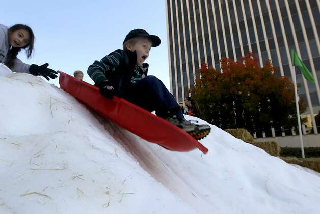 A boy rides a sled at the annual Winter Wonderland celebration in San Rafael, Calif. on Saturday, Nov. 26, 2011. Forty tons of snow was piled up on A Street for children to slide down with sleds, but with possible cuts to the city's redevelopment funds, organizers are worried this may be last year for the popular holiday event. Photo: Paul Chinn, The Chronicle
