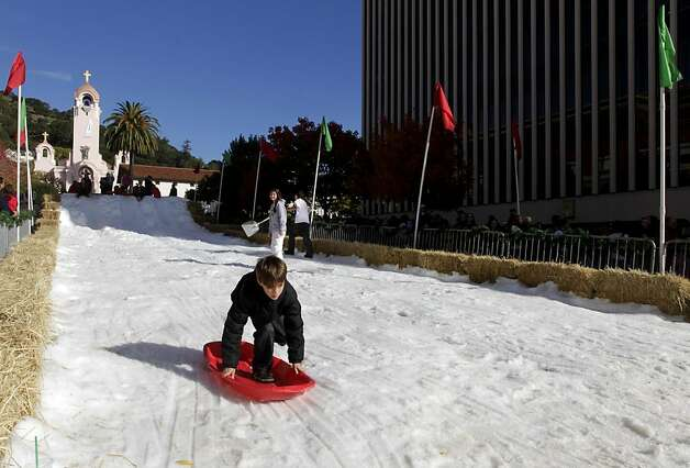 A sledder finishes his ride on a snowy slope at the annual Winter Wonderland celebration in San Rafael, Calif. on Saturday, Nov. 26, 2011. Forty tons of snow was piled up on A Street for children to slide down with sleds, but with possible cuts to the city's redevelopment funds, organizers are worried this may be last year for the popular holiday event. Photo: Paul Chinn, The Chronicle