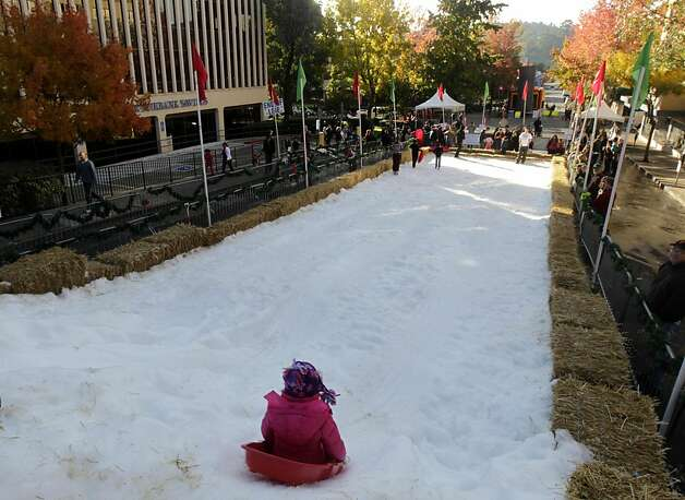A sledder rides down a snowy slope at the annual Winter Wonderland celebration in San Rafael, Calif. on Saturday, Nov. 26, 2011. Forty tons of snow was piled up on A Street for children to slide down with sleds, but with possible cuts to the city's redevelopment funds, organizers are worried this may be last year for the popular holiday event. Photo: Paul Chinn, The Chronicle