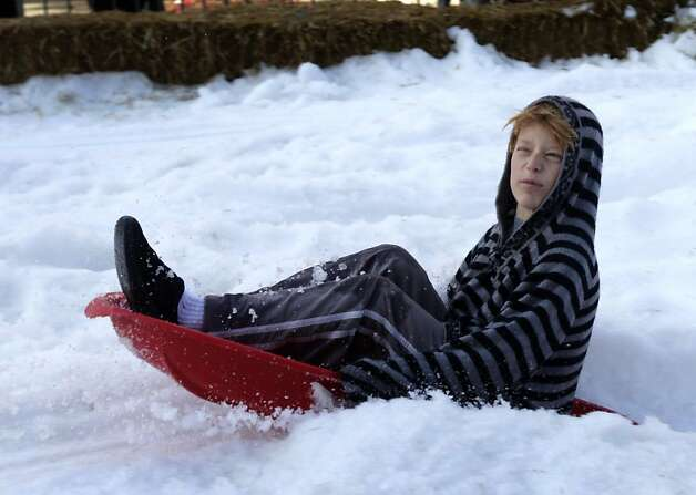 Leaf Allen, 10, sprays snow while sledding at the annual Winter Wonderland celebration in San Rafael, Calif. on Saturday, Nov. 26, 2011. Forty tons of snow was piled up on A Street for children to slide down with sleds, but with possible cuts to the city's redevelopment funds, organizers are worried this may be last year for the popular holiday event. Photo: Paul Chinn, The Chronicle