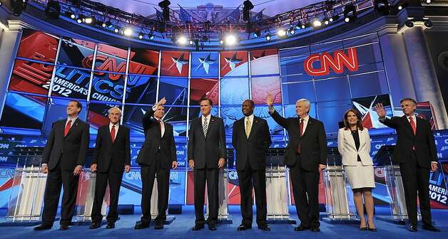 Republican presidential candidates arrive on stage prior to the start of the Republican presidential debate on national security November 22, 2011 at the Daughters of the American Revolution (DAR) Constitution Hall in Washington, DC. The debate is hosted by CNN in partnership with the Heritage Foundation and the American Enterprise Institute. From left are: Former Pennsylvania senator Rick Santorum; Texas Rep. Ron Paul; Texas Gov. Rick Perry; former Massachusetts governor Mitt Romney; businessman Herman Cain; for House speaker Newt Gingrich; Minnesota Rep. Michele Bachmann; and former Utah governor Jon Huntsman. AFP PHOTO / Mandel NGAN (Photo credit should read MANDEL NGAN/AFP/Getty Images) Photo: Mandel Ngan, AFP/Getty Images