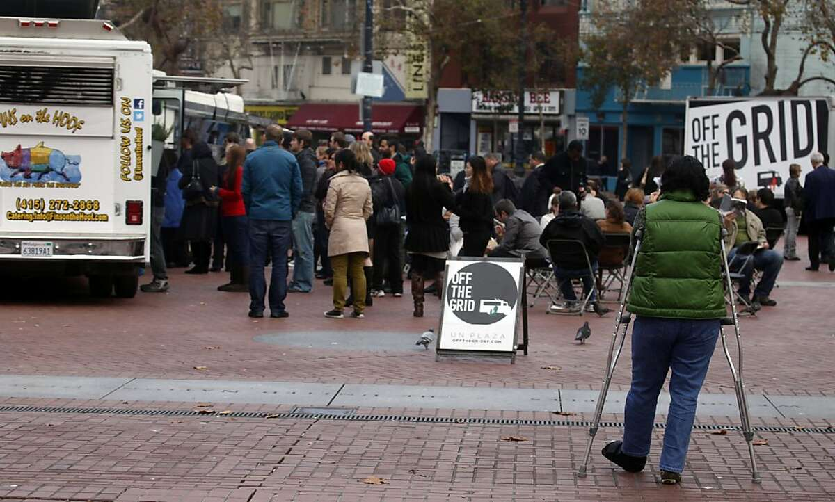 Long lines form at the Fins on the Hoof truck. Six food trucks offering a verity of lunch items at International Plaza in San Francisco Saturday November 19, 2011. Ran on: 11-27-2011 A crowd gathers at a half-dozen food trucks at S.F.s International Plaza. Restaurant owners say the mobile food venders have an unfair advantage.