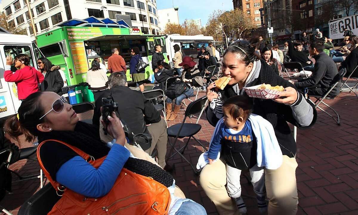 Dee Cadavillo takes pictures of her sister Andi Cadavillo both from San Jose and nephew James Rances 11 months old as they dig into lunch at International Plaza Saturday November 19, 2011.