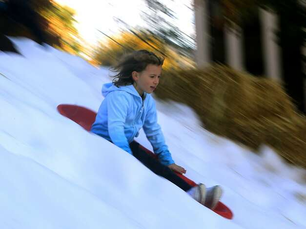 A young thrillseeker rides a sled on a snowy slope at the annual Winter Wonderland celebration in San Rafael, Calif. on Saturday, Nov. 26, 2011. Forty tons of snow was piled up on A Street for children to slide down with sleds, but with possible cuts to the city's redevelopment funds, organizers are worried this may be last year for the popular holiday event. Photo: Paul Chinn, The Chronicle
