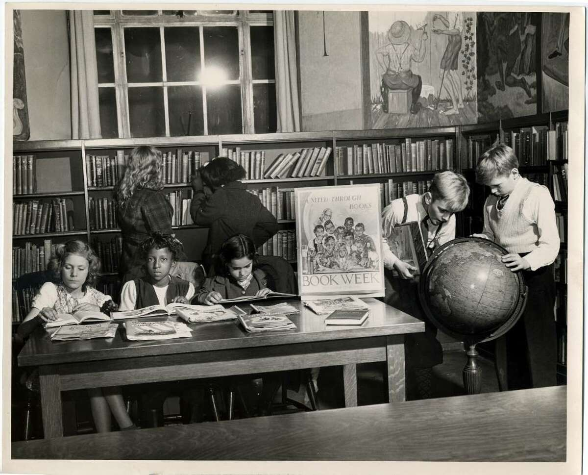 The photograph was taken in 1944 in what is now the Popular Library of the Burroughs-Saden Building of the Bridgeport Public Library on the corner of State and Broad streets in downtown Bridgeport. Back then, it was the library's children's room.The photo was taken to promote National Children's Book Week, which fell on the second full week of November of that year.