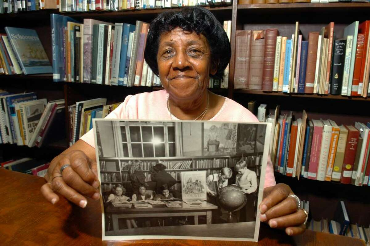 Louise Dent, of Bridgeport, poses in the main Burroughs-Saden Branch of the Bridgeport Public Library, in Bridgeport, Conn. on Oct. 22nd, 2009. She holds a vintage photograph in which she appears, taken at the library in 1944, when she was 11-years old. The photograph, from the Historic Collections of the Bridgeport Public Library, shows Dent and other school children taking part in a National Book Week event.
