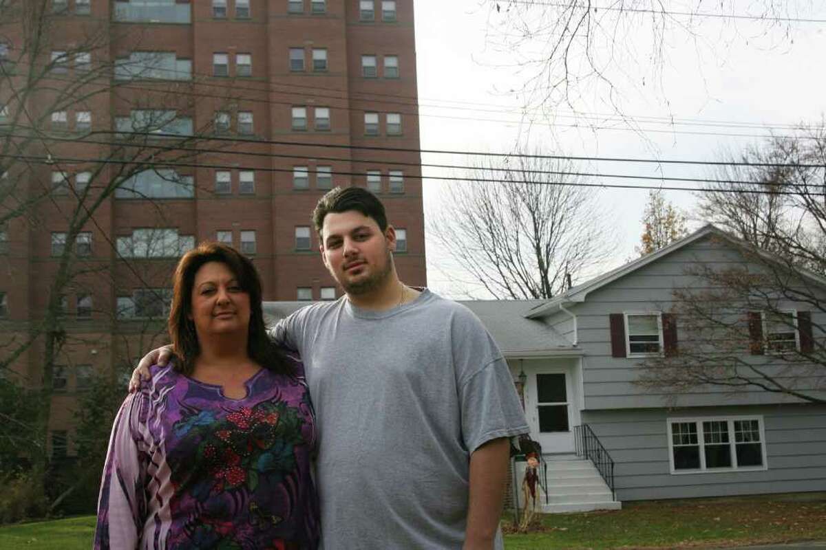 Cheryl Lee Norko and her son, Gerry, stand in front of their Bridgeport home and Sacred Heart University's Roncalli Hall, a student dorm, on Sunday, November 27, 2011. Norko's life was recently threatened when she asked students to be quiet.
