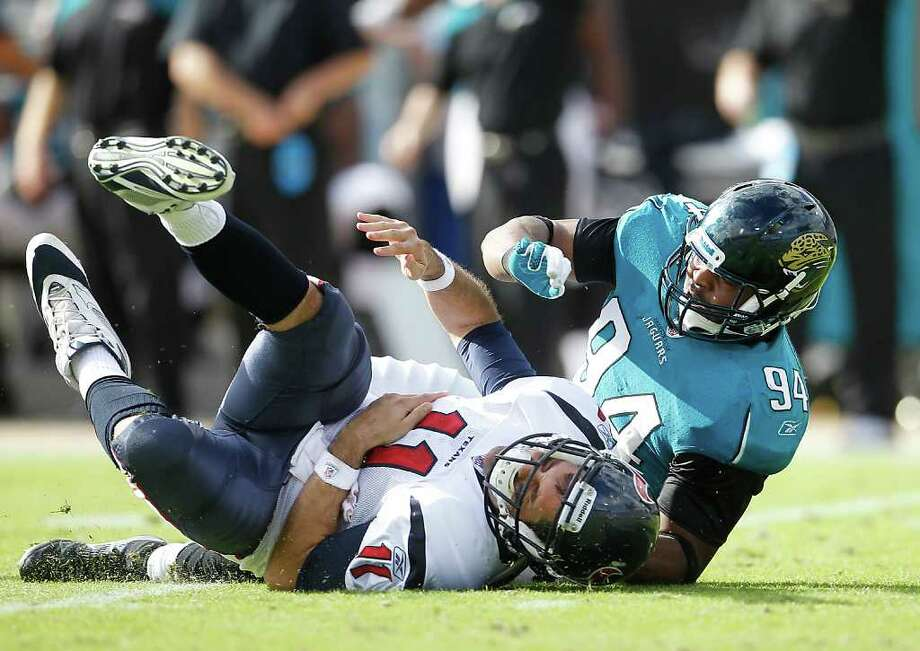 Houston Texans quarterback Matt Leinart (11) lies on the ground after getting his arm pulled back by Jacksonville Jaguars defensive end Jeremy Mincey (94), he was injured on this play during the second quarter of an NFL football game at EverBank Field inJacksonville, FL, Nov. 27, 2011. Photo: Karen Warren, Houston Chronicle / © 2011 Houston Chronicle
