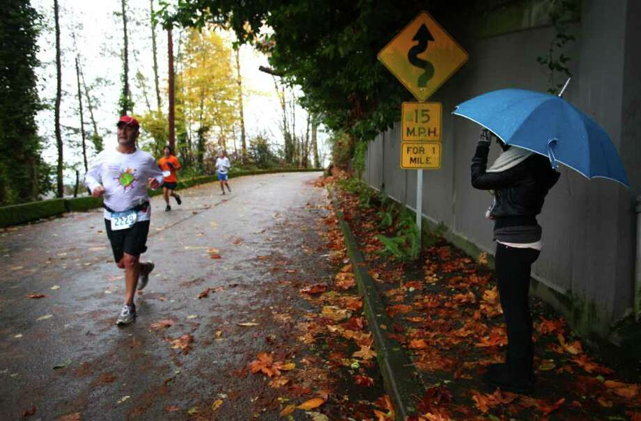 Tara McGrath waits for her dad to pass on East Interlaken Boulevard during the Seattle Marathon on Sunday, November 27, 2011. Photo: JOSHUA TRUJILLO / SEATTLEPI.COM
