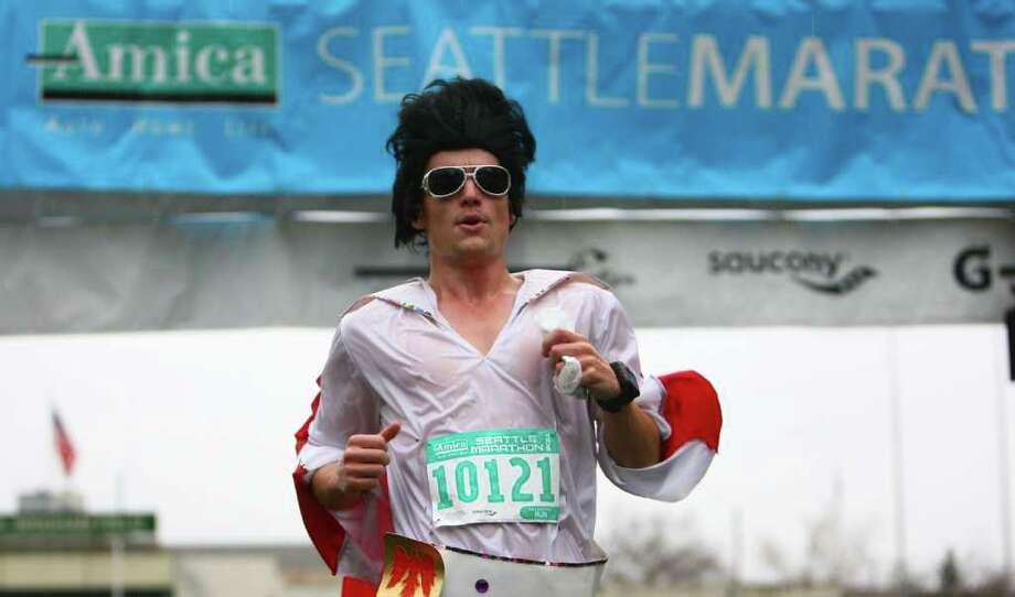 A runner dressed as Elvis crosses the finish line in Memorial Stadium during the Seattle Marathon on Sunday, November 27, 2011. Photo: JOSHUA TRUJILLO / SEATTLEPI.COM