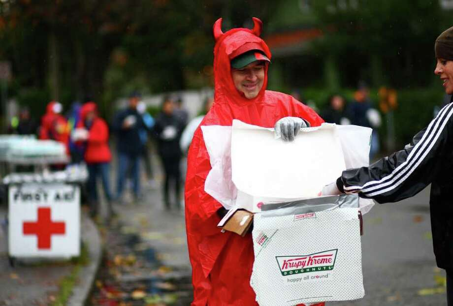 David Peterman hands out doughnuts to competitors on the course during the Seattle Marathon on Sunday, November 27, 2011. Photo: JOSHUA TRUJILLO / SEATTLEPI.COM