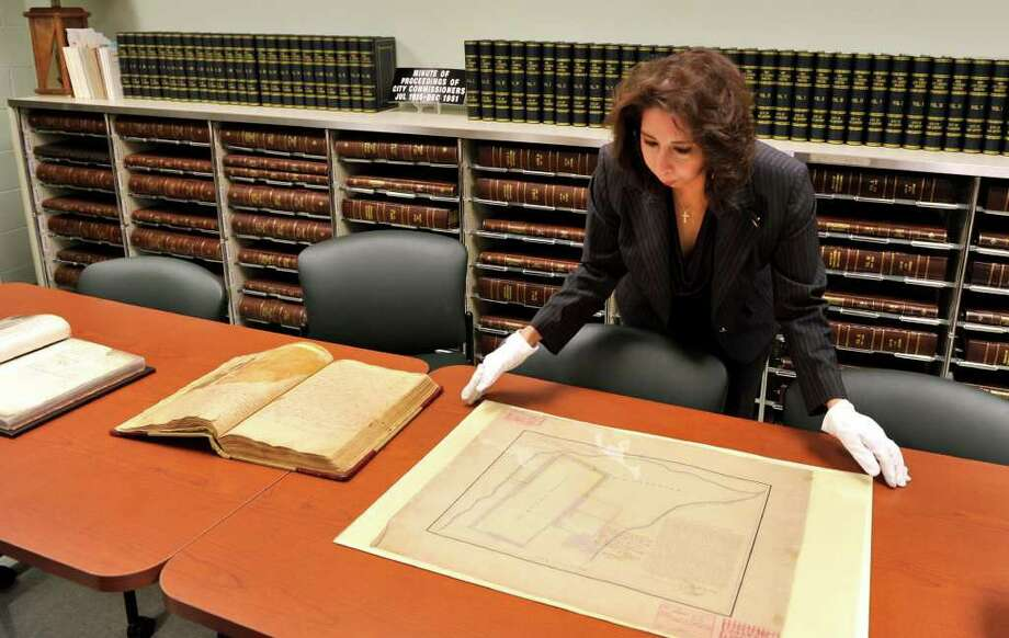 San Antonio City Clerk Leticia Vacek looks at an 1885 reproduction of the original Alamo plat. It is just one of the maps that has been digitized by the City Clerk's office in a transition to online capability. Photo: Photo By Robin Jerstad/Special To The Express-News
