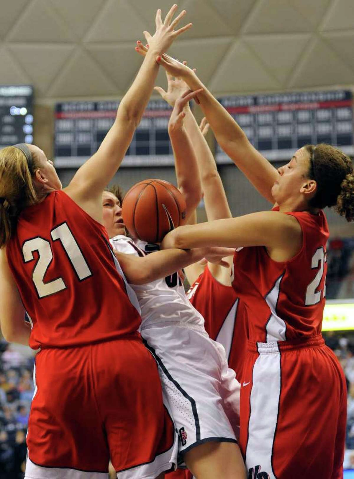 Connecticut's Stefanie Dolson, center, is trapped between Dayton's Ally Malott (21), Casey Nance (22) and Justine Raterman, rear, in the first half of an NCAA college basketball game in Storrs, Conn., Sunday, Nov. 27, 2011. (AP Photo/Jessica Hill)