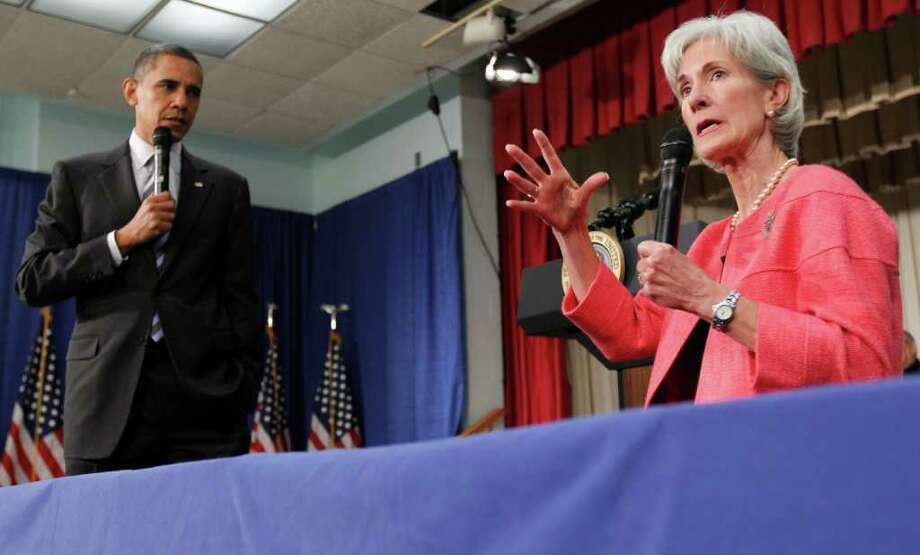 "FILE - In this June 8, 2010 file photo, President Barack Obama listens as Health and Human Services Secretary Kathleen Sebelius speaks during a town hall meeting on the Affordable Care Act, at the Holiday Park Multipurpose Senior Center in Wheaton, Md. Medicare's prescription coverage gap is getting noticeably smaller and easier to manage this year for millions of older and disabled people with high drug costs. The ""doughnut hole""will shrink about 40 percent for those unlucky enough to land in it, according to new Medicare figures provided in response to a request from The Associated Press.  (AP Photo/Alex Brandon, File) Photo: Alex Brandon / AP"