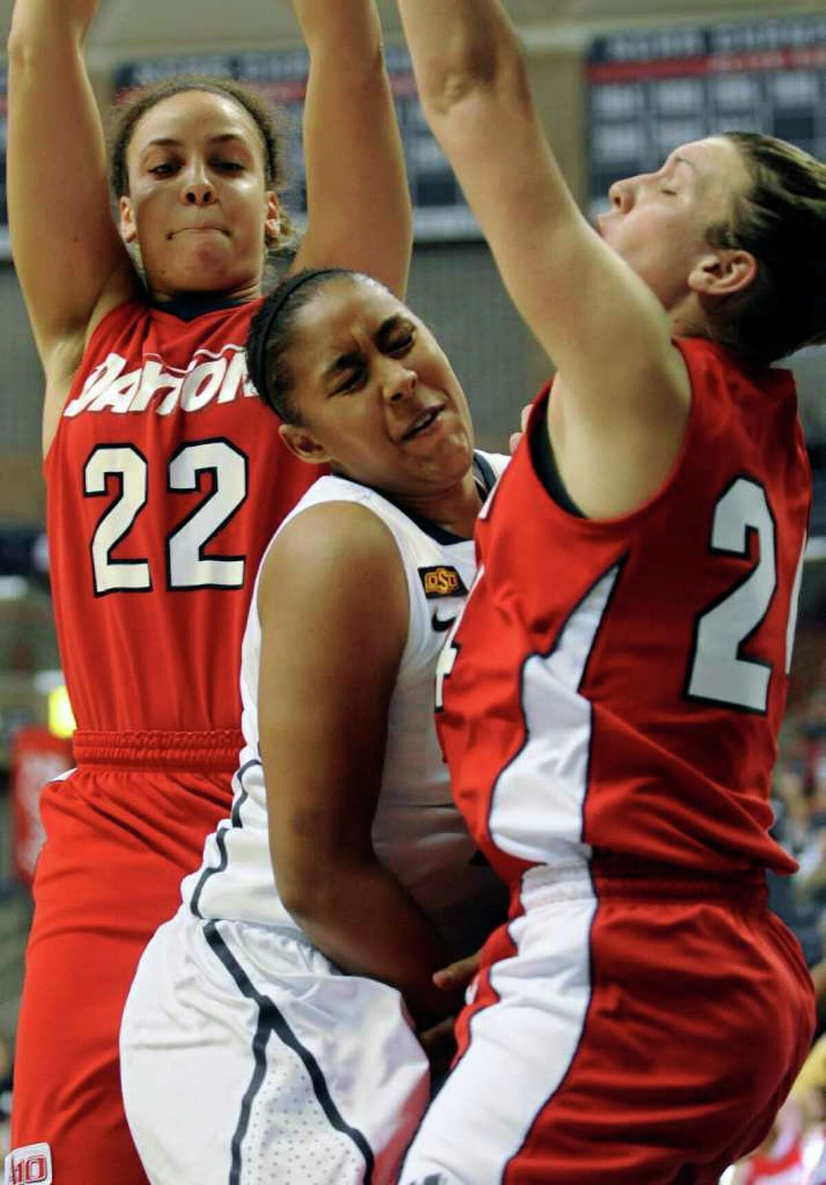 Connecticut's Kaleena Mosqueda-Lewis, center, is caught between Dayton's Casey Nance, left, and Andrea Hoover, right, as she drives to the basket in the first half of an NCAA college basketball game in Storrs, Conn., Sunday, Nov. 27, 2011. Mosqueda-Lewis led Connecticut with 23 points in the 78-38 victory. It was the team's 89th straight win at home to set an NCAA record. (AP Photo/Jessica Hill)
