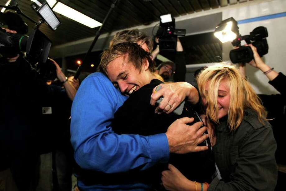 JEFF ROBERSON : ASSOCIATED PRESS MISSOURI: Derrik Sweeney, 19, gets hugs from his father Kevin, left, and sister Ashley in  the St. Louis airport. Photo: Jeff Roberson / AP