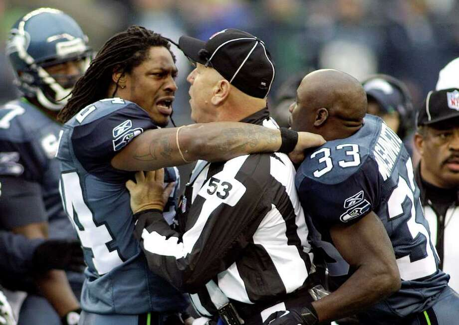 Umpire Garth DeFelice, third from left, holds back Seattle Seahawks' Marshawn Lynch, second from left, and Leon Washington (33) in a shoving match during the coin toss in the first quarter of an NFL football game against the Washington Redskins, Sunday, Nov. 27, 2011, in Seattle. Photo: AP